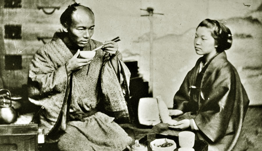 Japanese Samurai Eating With Chopsticks While Wife Patiently Watches Him Eating